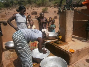 Women collecting water at a well in rural Burkina Faso, West Africa
