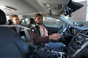 A University of Utah research assistant introduces a participant in new distracted driving studies to special devices designed to gauge mental distraction during road tests.