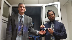 Michael Free (left) holds a light emitting diode and Prashant Sarswat (right) holds carbon dots in suspension.