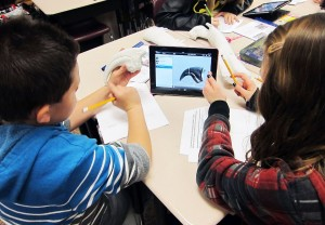 Two students examine a virtual 3-D model of a dinosaur bone from the museum's fossil collections.