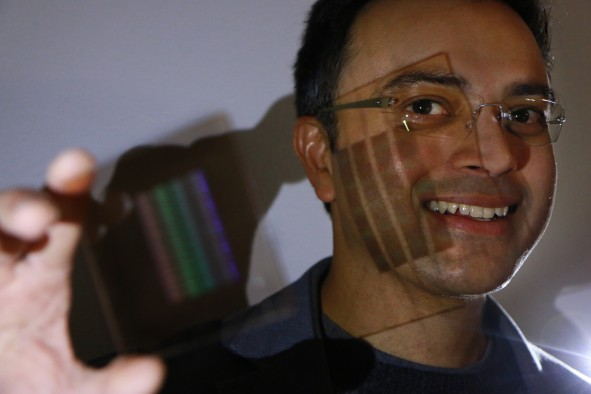 University of Utah electrical and computer engineering professor Rajesh Menon holds up the prototype of the first flat thin camera lens that he and his team developed. Menon and his doctoral students, Peng Wang and Nabil Mohamma, have developed a new kind of optical lens that is flat and ultrathin instead of the traditionally curved lens but can still focus all the colors of light to one point. The new lens can be used in cameras and other devices such as smartphones where the lens does not have to jet out of the body. Other applications of this potential lens system include medical devices in which thinner and lighter endoscopes can peer into the human body. It also could be used for drones or satellites with lighter cameras in which reducing weight is critical. Future smartphones could come with high-powered cameras that don't require the lens jetting out from the phone's thin body, such as the lens does now for the iPhone 6S.