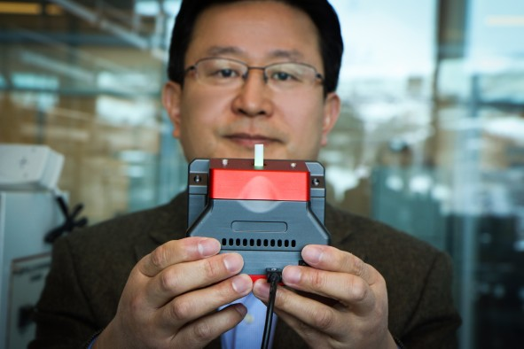 University of Utah materials science and engineering professor Ling Zang holds up a prototype handheld detector his company is producing that can sense explosive materials and toxic gases. His research team developed a new material for the detector that can sense alkane fuel, a key ingredient in such combustibles as gasoline, airplane fuel and homemade bombs.