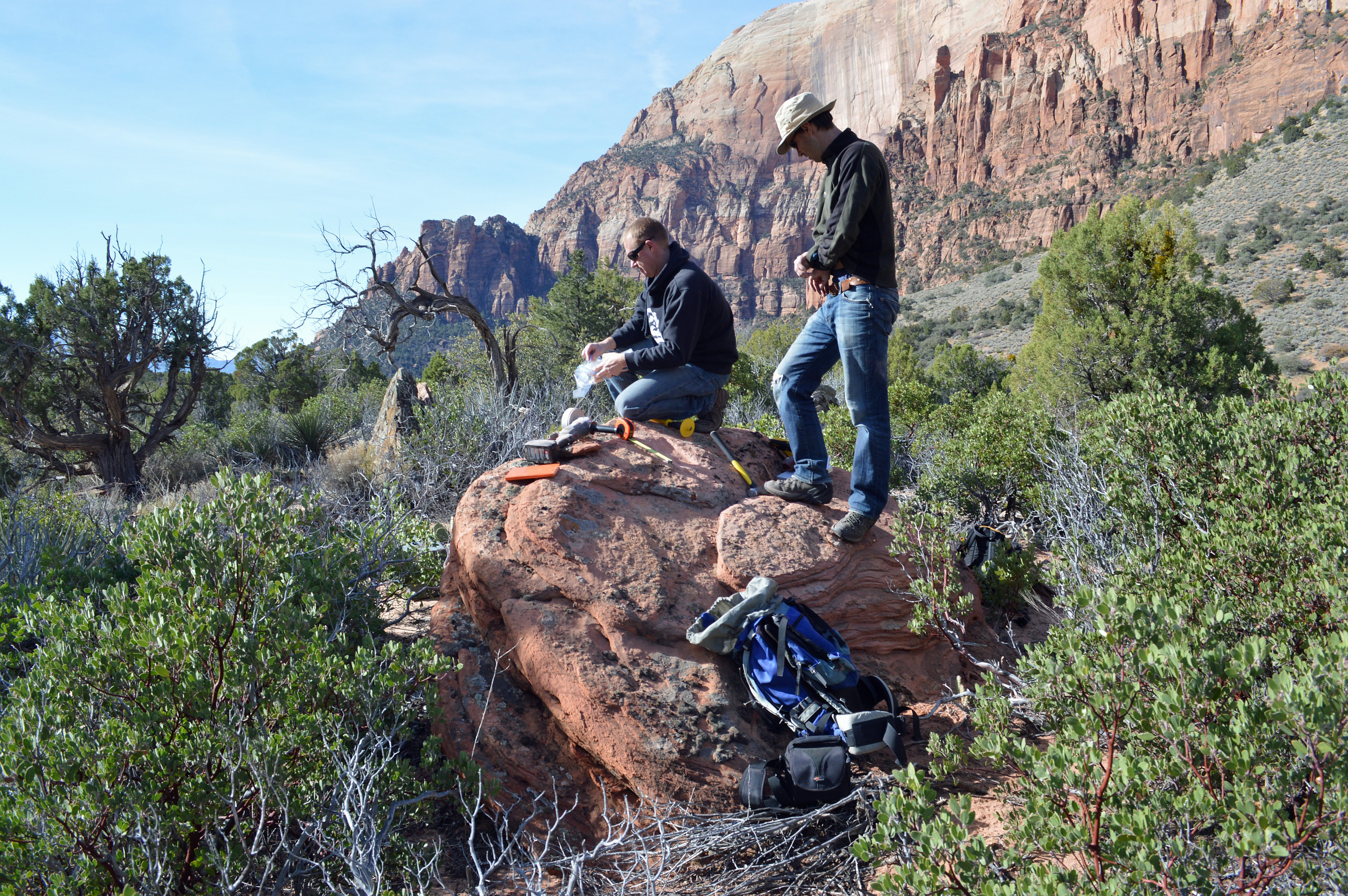 Volunteer Scott Castleton and University of Utah geologist Jeff Moore collect rock samples from boulders for a new study that provides the first direct date – 4,800 years ago – for a a gargantuan landslide in what is now Zion National Park, Utah.
