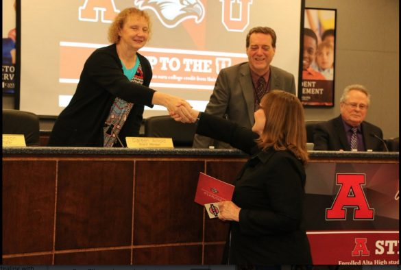 University of Utah Senior Associate Vice President of Academic Affairs Martha Bradley shakes hands with Canyons Board of Education members Clareen Arnold and Steve Wrigley.