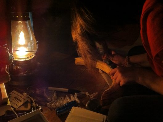 Kendra Chritz sampling hippo canine enamel by kerosene lamplight in Queen Elizabeth National Park.