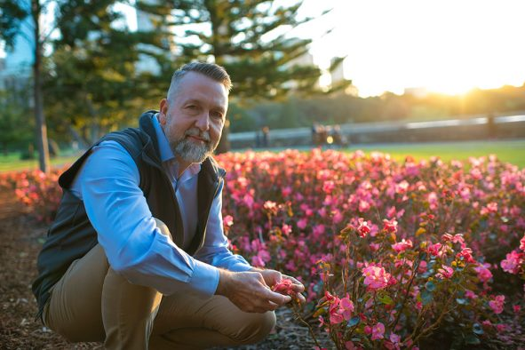 Jimmy L. Turner, new executive director of the Red Butte Garden, cradles some pink tulip-like flowers in golden light.