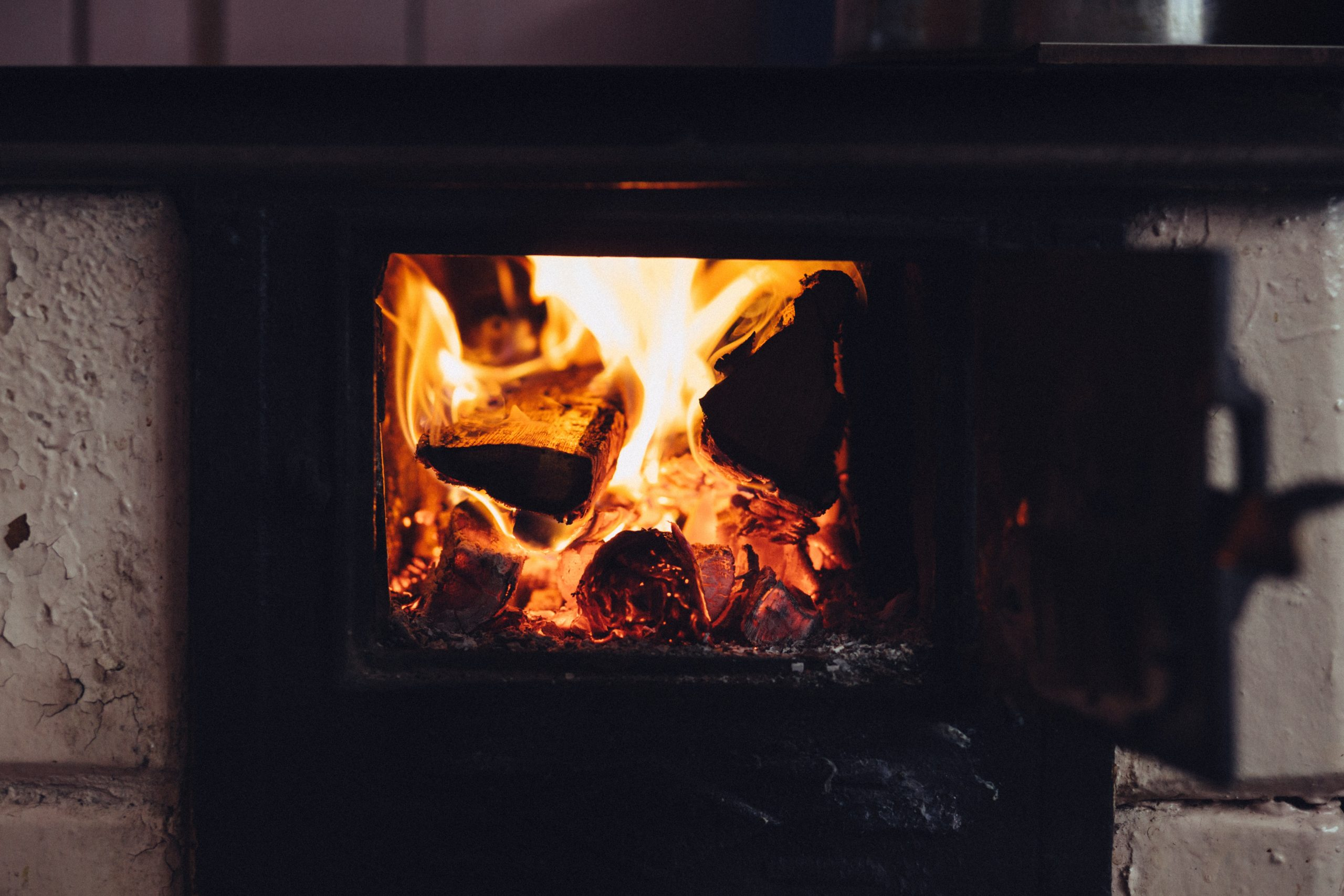 A bonfire burning in a black wood-burning stove.